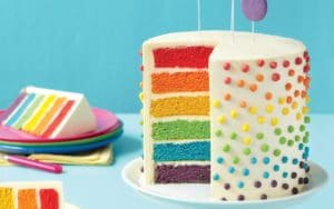 A frosted layer cake sliced open to reveal six layers in rainbow colors.