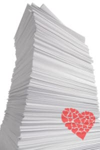Giant looming stack of white paper with a red heart on the side