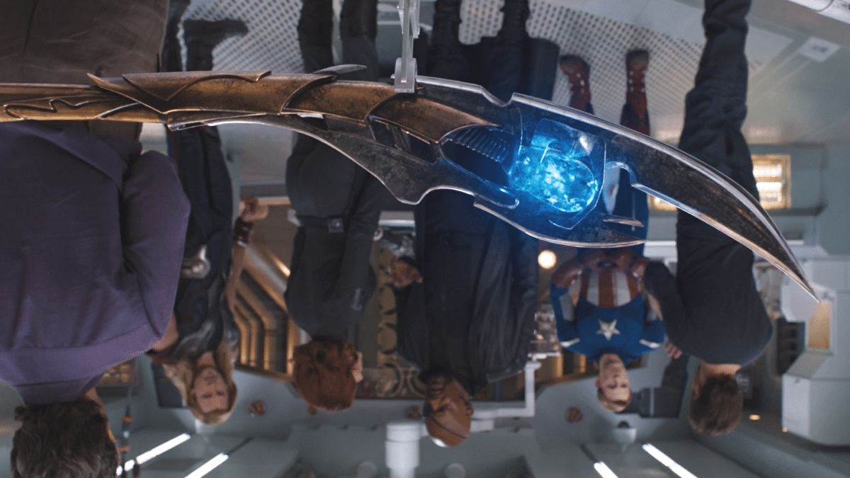 screenshot from The Avengers showing Loki's glowing spear in the foreground while, upside down, Nick Fury, Natasha Romanoff, Bruce Banner, Steve Rogers and Tony Stark argue in the background, in the lab of the helicarrier,