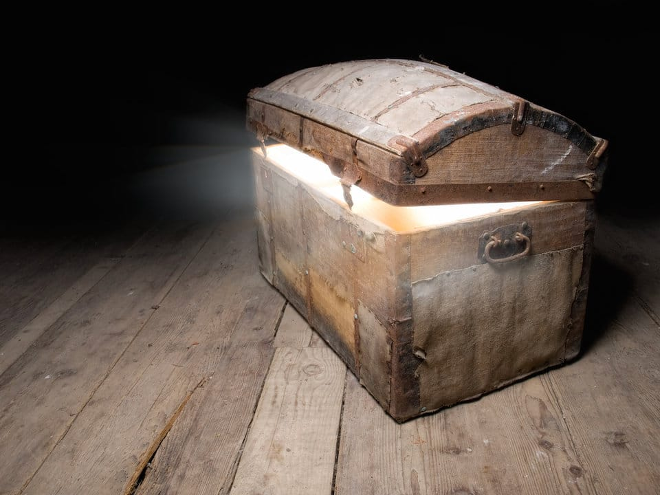 An antique wooden chest on a distressed wood plank floor, just cracked open with bright white light spilling out.